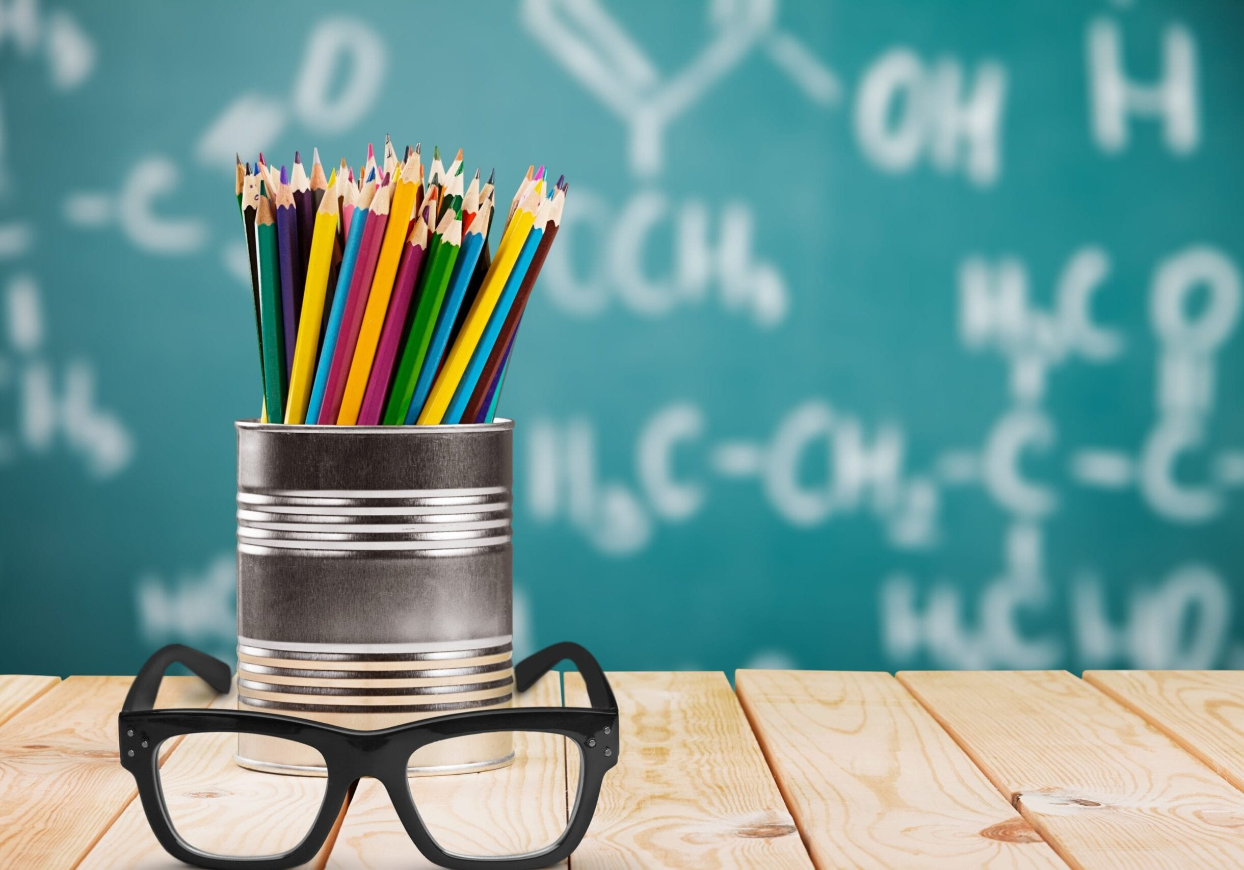 Classroom image: Pot of pencils and pair of glasses on desk in foreground with blackboard with writing on it blurred in background